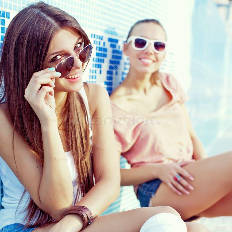 Zwei schöne junge Mädchen auf dem Boden eines leeren Pools lizenzfreie stockfotografie