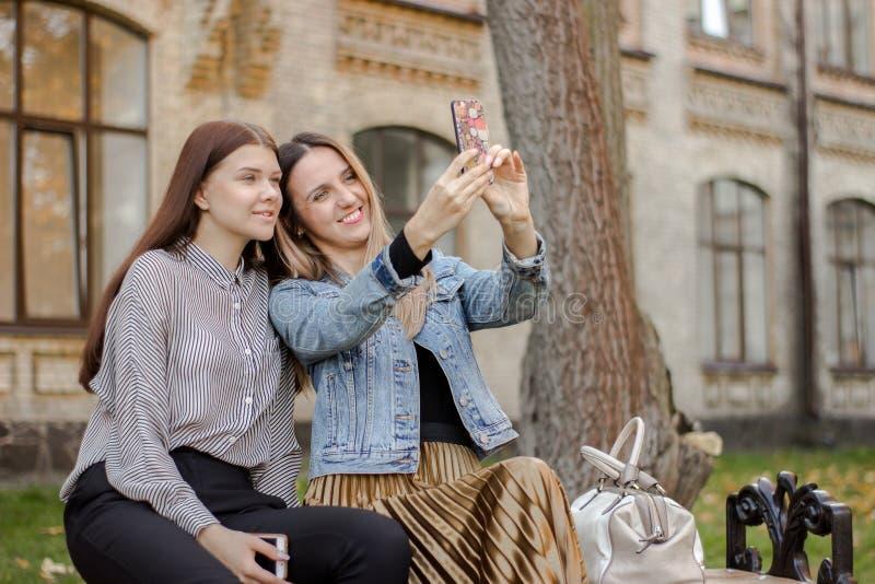 Zwei schöne junge Mädchen, die selfie am Telefon beim Sitzen auf einer Bank im Herbstpark nahe der Universität nehmen lizenzfreies stockfoto