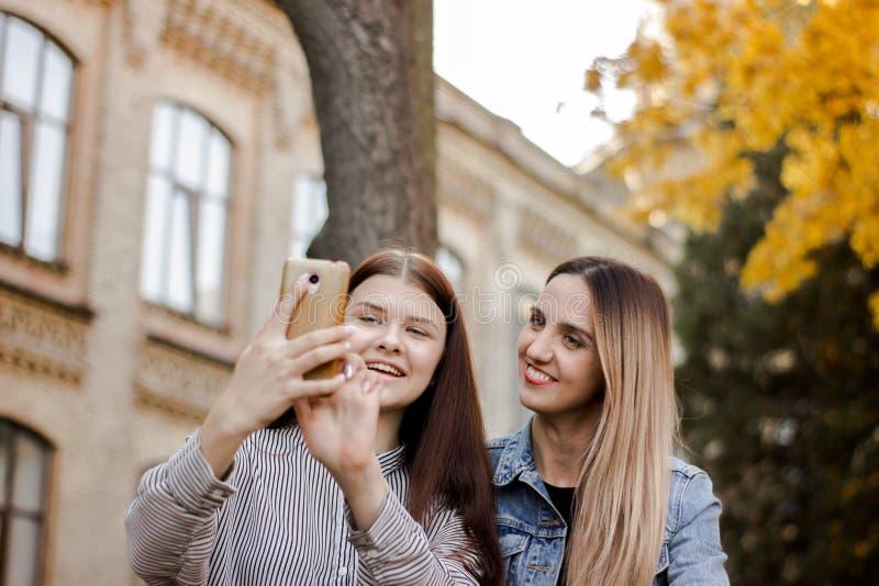 Zwei schöne junge Mädchen, die selfie am Telefon im Herbstpark nahe der Universität nehmen stockfotografie