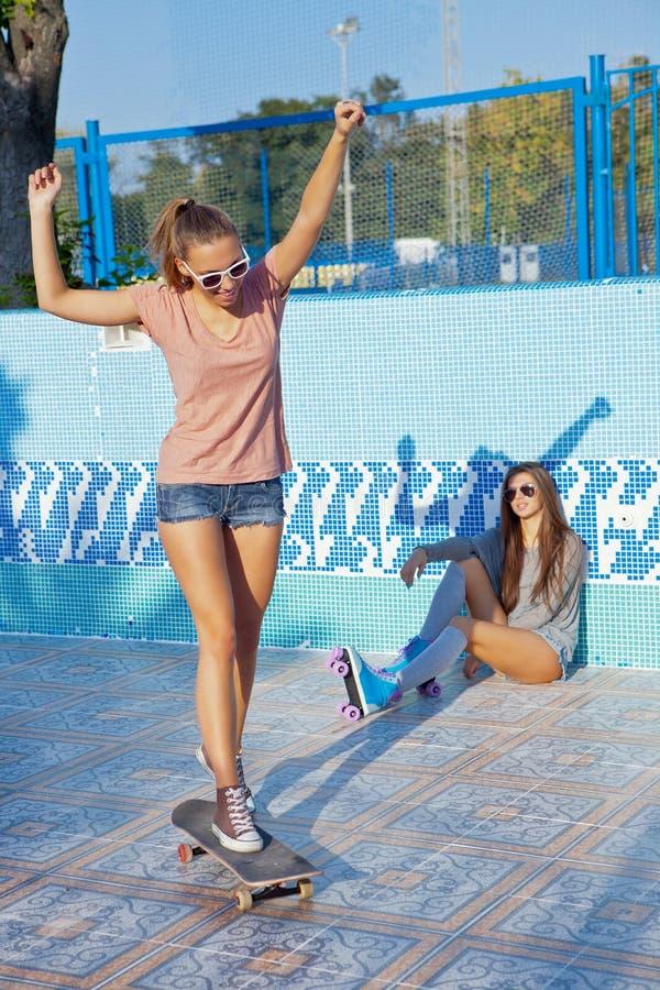 Zwei schöne junge Mädchen, die Sonnenbrille in einem leeren Pool tragen lizenzfreie stockbilder