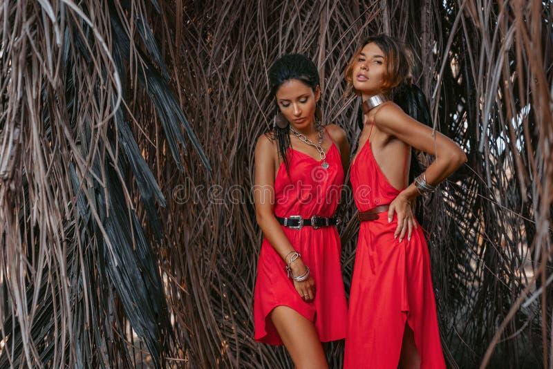 Zwei schöne junge moderne Modelle in den roten Kleidern draußen bei Sonnenuntergang stockbilder