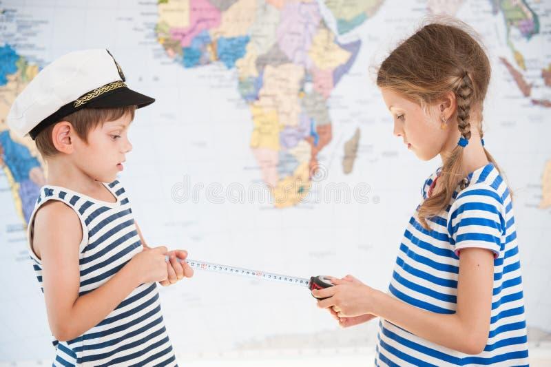 Zwei schöne Kinder im Maßabstand der gestreiften Hemden des Seemanns auf Weltkarte mit messendem Band stockfoto