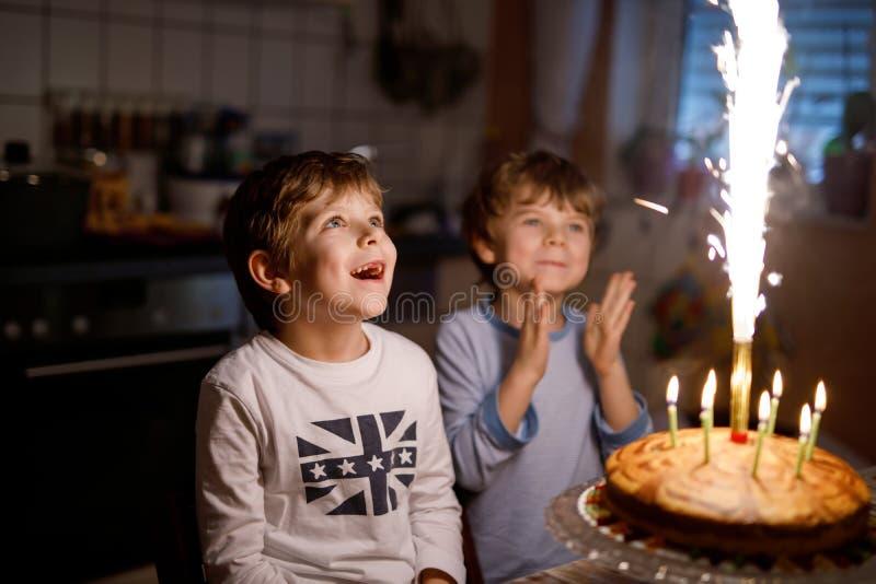 Zwei schöne Kinder, kleine Vorschuljungen, die Geburtstag feiern und Kerzen durchbrennen stockfotografie