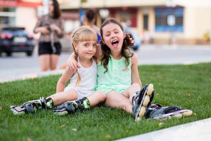 Zwei schöne kleine Schwestern in Rollschuhe lizenzfreie stockfotografie