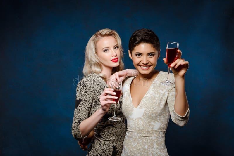 Zwei schöne Mädchen in den Abendkleidern Lächeln, Weingläser halten lizenzfreie stockbilder