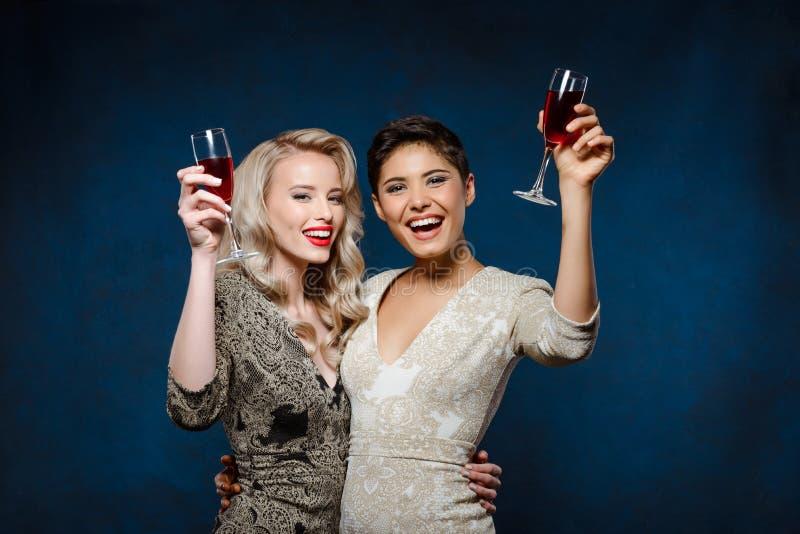 Zwei schöne Mädchen in den Abendkleidern Lächeln, Weingläser halten stockfotos