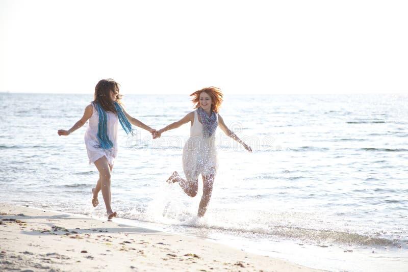 Zwei schöne Mädchen, die auf den Strand laufen. lizenzfreie stockfotografie
