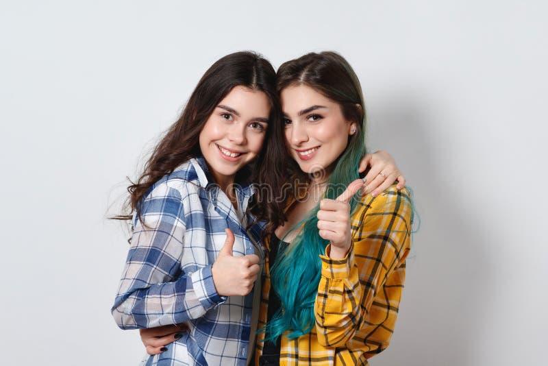 Zwei schöne Mädchen, die Daumen lächeln und sich zeigen Auf weißem Hintergrund lizenzfreie stockfotos