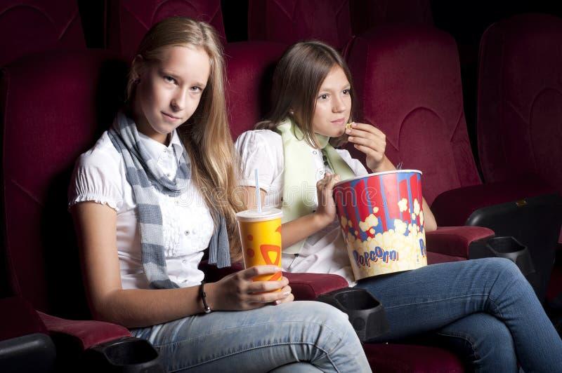 Zwei schöne Mädchen, die einen Film am Kino überwachen lizenzfreies stockbild