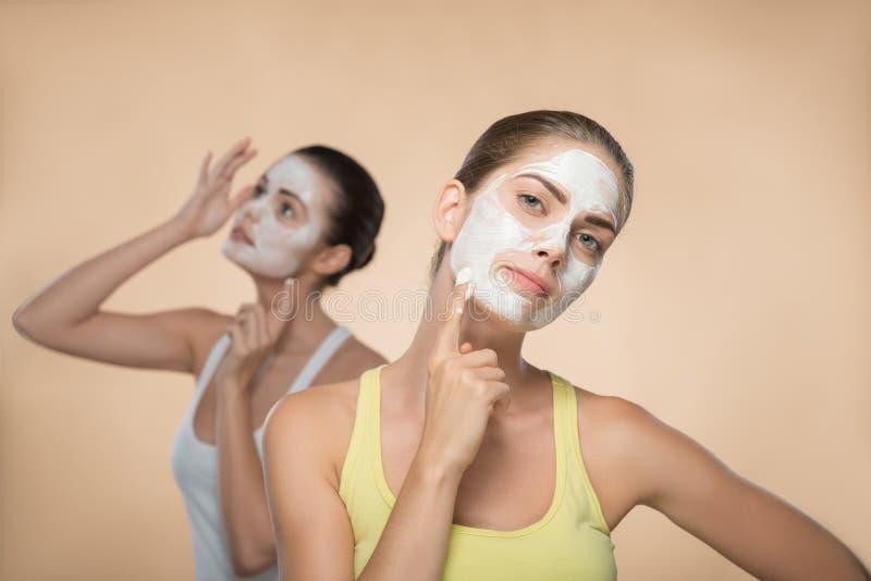 Zwei schöne Mädchen, die Gesichtssahnemaske anwenden und lizenzfreie stockfotos