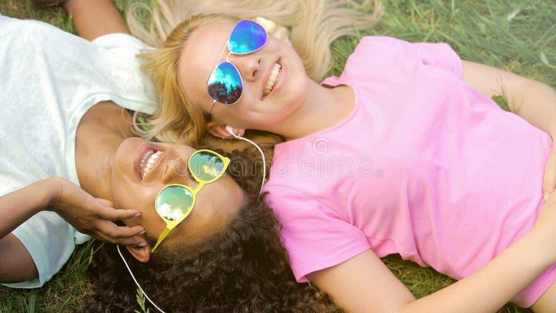 Zwei schöne Mädchen, die Musik auf dem Smartphone, auf dem Campus liegend auf Gras hören stockfotografie