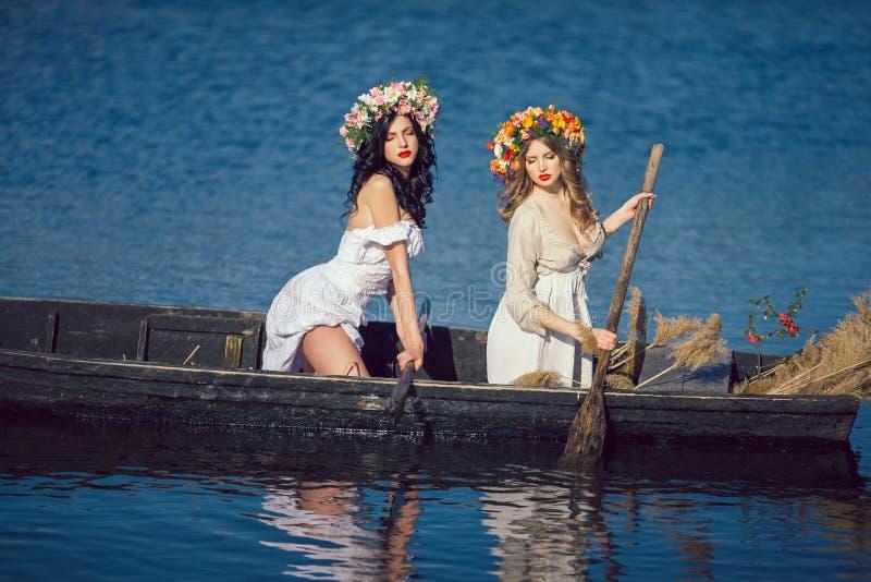 Zwei schöne Mädchen im Boot lizenzfreie stockfotografie