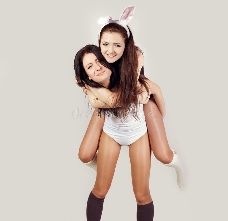 Zwei schöne Mädchen lassen Spaß herum täuschen im Studio auf weißem weißen und schwarzen Bodysuit des Hintergrundes und den Gamas stockbilder