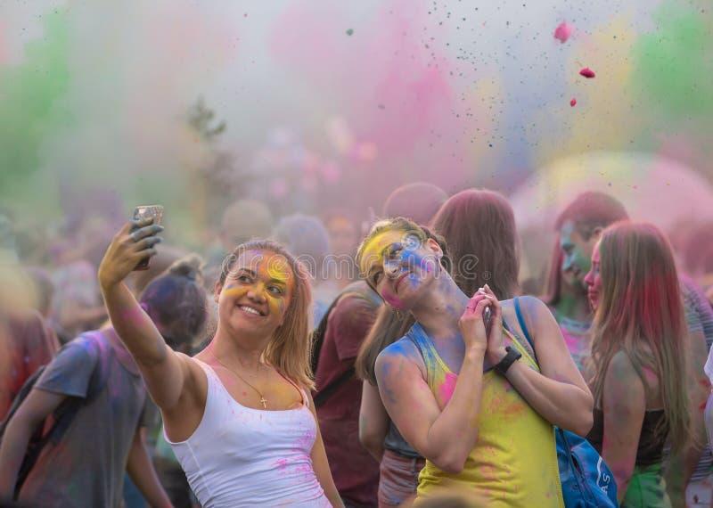 Zwei schöne Mädchen machen selfie während des Holi kriegs- Spielens mit farbigen Farben trocken stockfoto