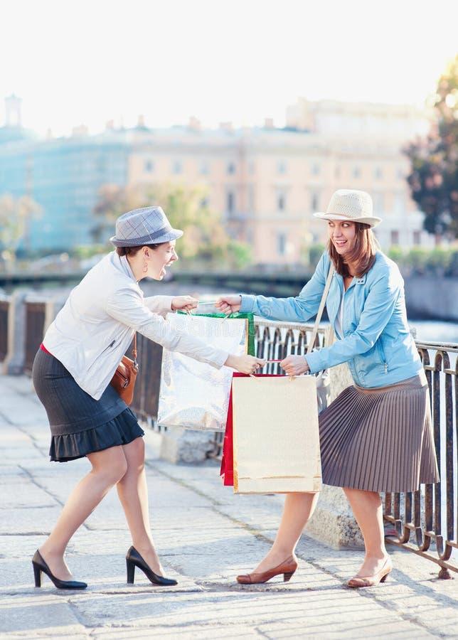 Zwei schöne Mädchen mit den Einkaufstaschen, die Kampf in der Stadt haben lizenzfreie stockfotos