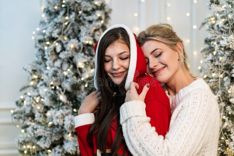 Zwei schöne Schwestern in den Strickjacken, die nahe dem Weihnachtsbaum umarmen stockfoto