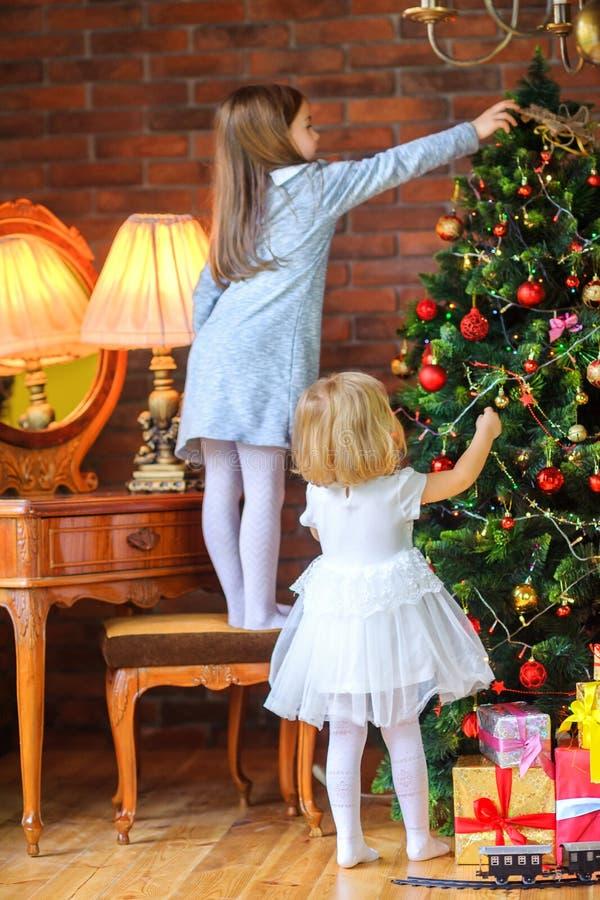 Zwei schöne Schwestern verzieren den Weihnachtsbaum stockfotografie