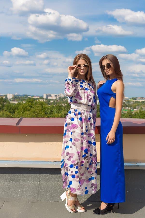 Zwei schöne sexy junge Freundinnen in krasiivyh langer modischer Kleidung in der Sonnenbrille, die auf der Terrasse unter dem hel lizenzfreie stockfotos