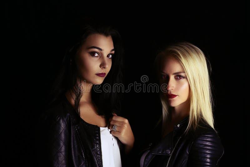 Zwei schöne Vampirsmädchen, die eine Lederjacke tragen lizenzfreies stockbild