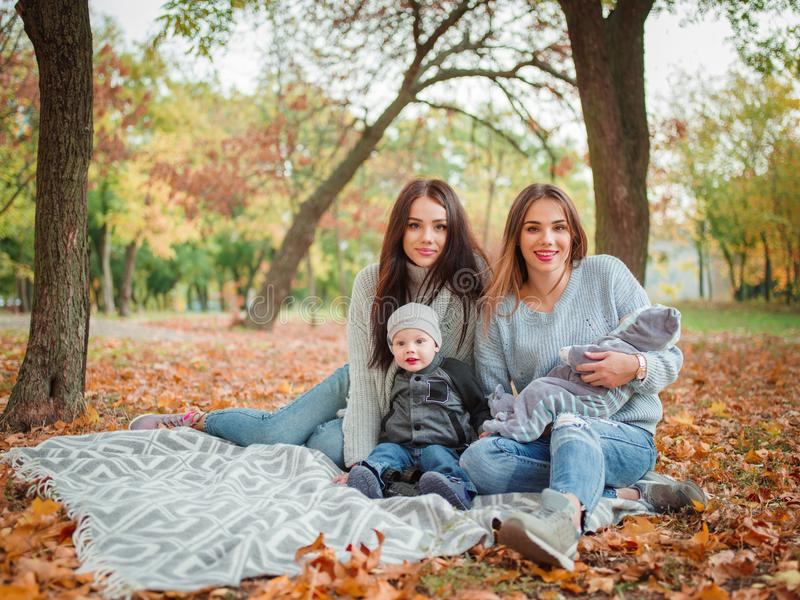 Zwei schöne Zwillingsmädchen, sitzen in einem Herbstpark mit ihren zwei Kleinkindern lizenzfreie stockfotos