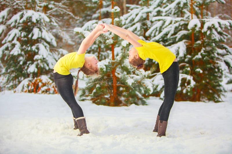 Zwei Schönheiten, die draußen Yoga im Schnee tun lizenzfreie stockbilder