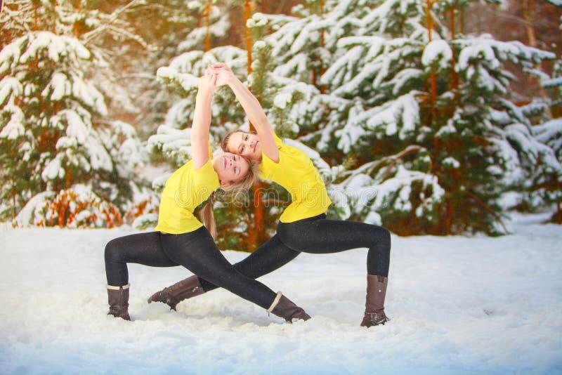Zwei Schönheiten, die draußen Yoga im Schnee tun stockbilder