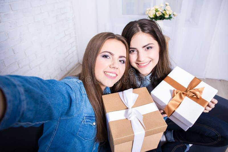 Zwei Schönheiten, die selfie Foto mit Geschenken beim Leben machen stockbild