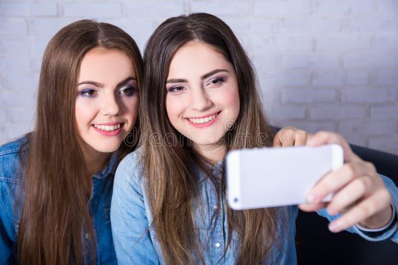 Zwei Schönheiten, die selfie Foto mit intelligentem Telefon machen stockfotos