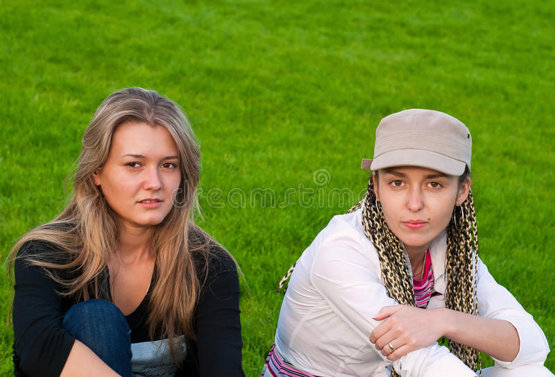 Zwei Schönheitsmädchen auf Gras lizenzfreies stockbild