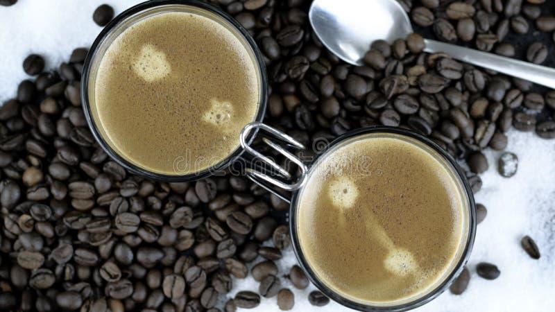 Zwei Schüsse Espresso sitzend in einem Bett von Kaffeebohnen lizenzfreie stockfotografie