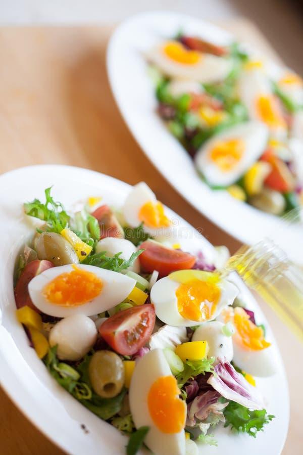 Zwei Schüsseln köstlicher frischer Salat mit Mozzarella, Eier, Oliven stockfotografie