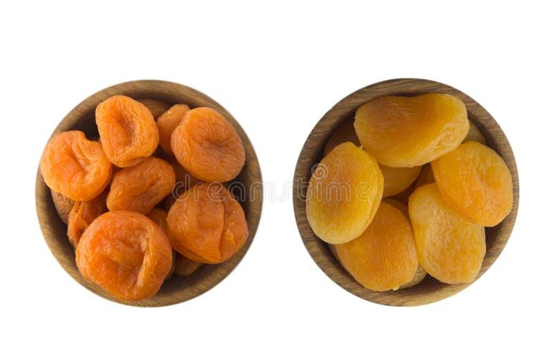 Zwei Schüsseln mit getrockneten Aprikosen in einer hölzernen Schüssel lokalisiert auf Weiß Trockenfrüchte mit Kopienraum für Text lizenzfreies stockbild