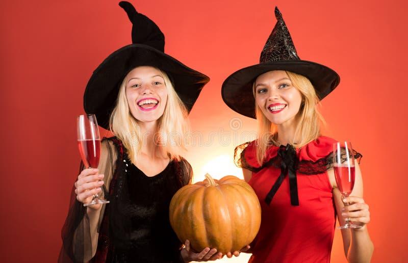 Zwei Sch?nheiten in den sexy Kost?men des Karnevals von Hexen bild Zwei gl?ckliche junge Frauen in den Schwarzen und Rotkleidern lizenzfreies stockfoto