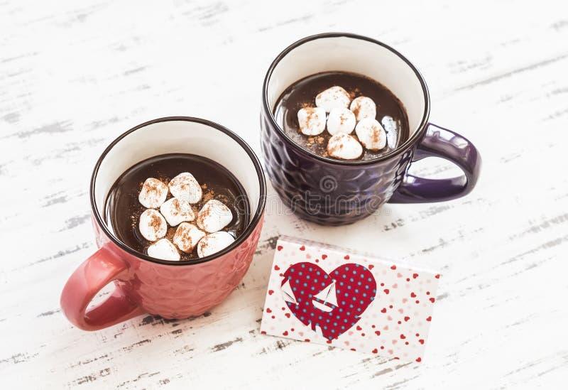 Zwei Schalen heiße Schokolade mit Eibischen und Valentinstagpostkarte lizenzfreie stockfotografie