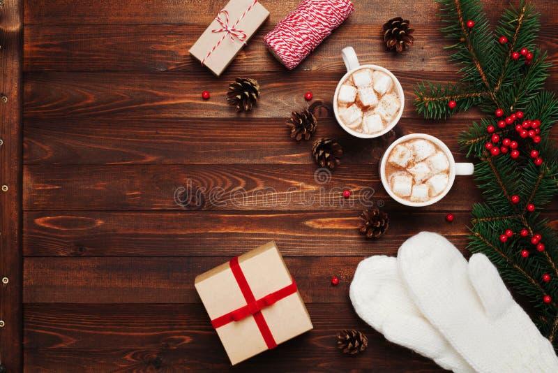 Zwei Schalen heißer Kakao oder Schokolade mit Eibisch, Geschenken, Handschuhen, Weihnachtsdekor und Tannenbaum auf hölzernem Hint stockfotografie
