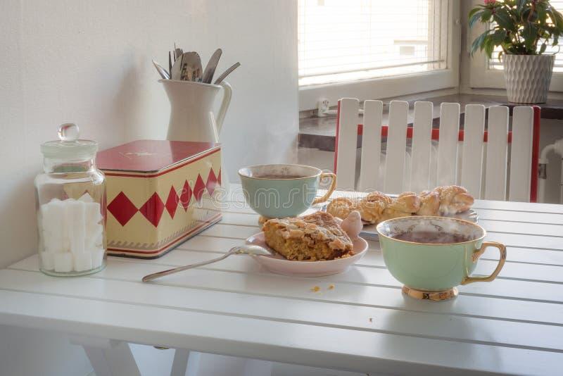 Zwei Schalen heißer Tee mit Kuchen auf einer weißen Tabelle stockbild