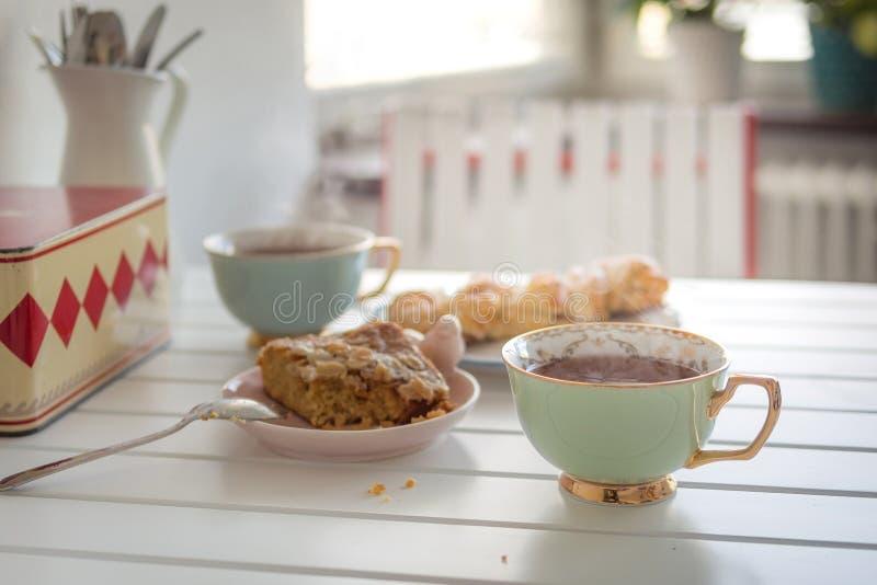 Zwei Schalen heißer Tee mit zwei Kuchen auf einer weißen Tabelle stockfoto