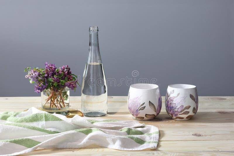 Zwei Schalen, Sch?ssel mit Wasser, Tuch, Fr?hlingsblumen auf dem h?lzernen Schreibtisch sonniger Morgen Fr?hst?ck stockbilder