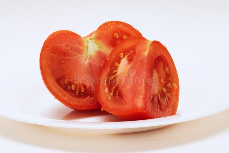 Zwei Scheiben von roten Tomaten auf einer weißen Platte lizenzfreie stockbilder