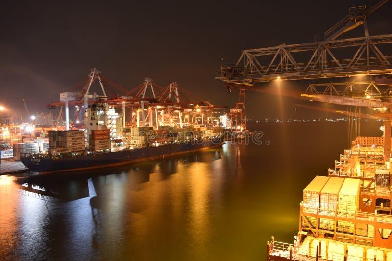 Zwei Schiffe längsseits am beschäftigten Containerbahnhof stockfotografie
