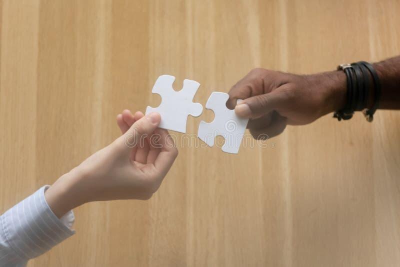 Zwei schließen sich das verschiedene männlich-weibliche Handhalten Puzzlen an stockfotos