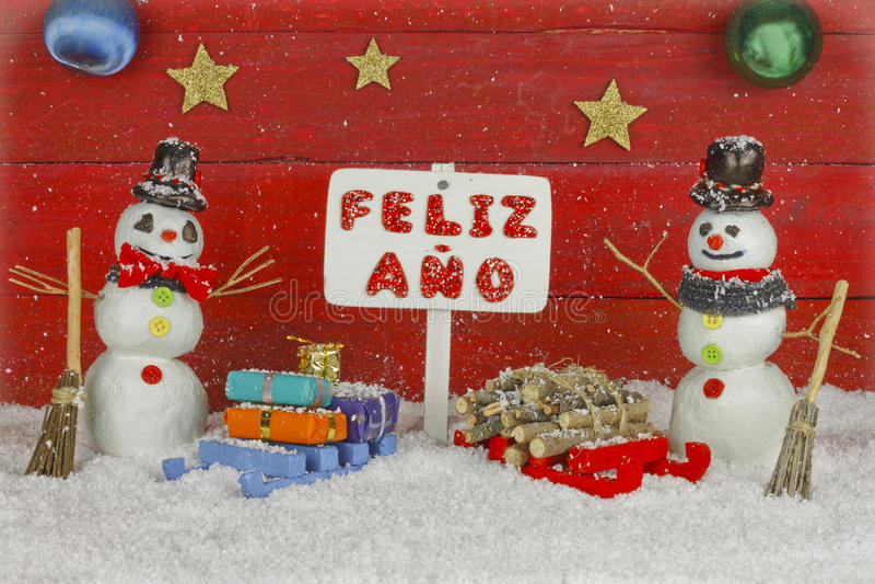 Zwei Schneemänner mit einem guten Rutsch ins Neue Jahr Wegweiser mit den Wörtern, die auf Spanischen geschrieben werden stockfotografie