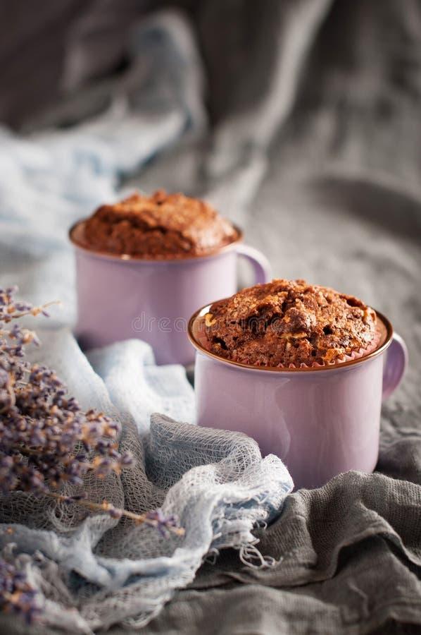 Zwei Schokoladenmuffins in den lila Schalen lizenzfreie stockbilder
