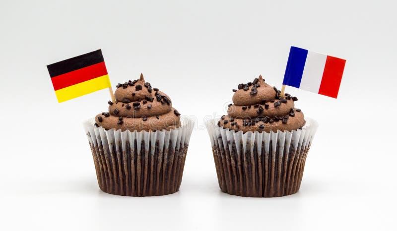 Zwei Schokoladensplitterstrudelkleine kuchen mit dreifarbiger französischer Flagge und deutsche Flaggenzahnstocher in ihnen lokal lizenzfreies stockbild