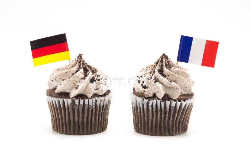 Zwei Schokoladenstrudelkleine kuchen mit dreifarbiger französischer Flagge und deutsche Flaggenzahnstocher in ihnen lokalisierten lizenzfreie stockfotografie