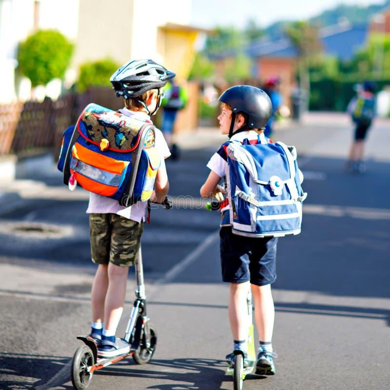 Zwei Schulkinderjungen im Schutzhelmreiten mit Roller in der Stadt mit Rucksack am sonnigen Tag Glückliche Kinder herein lizenzfreies stockfoto