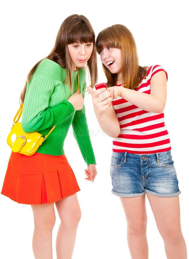 Zwei Schulmädchen, die etwas im Mobile überwachen stockbilder