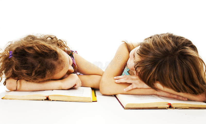 Zwei Schulmädchen, die am Schreibtisch ist müde studieren stockfotografie