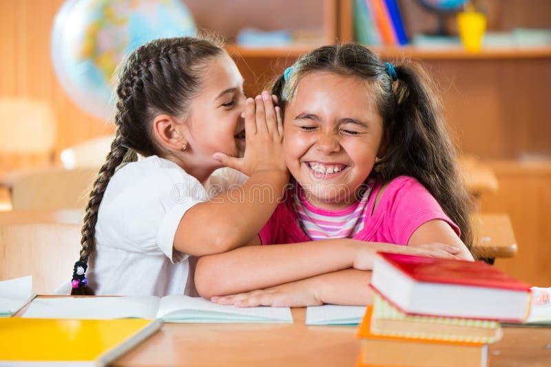 Zwei Schulmädchen, die Spaß an der Schule haben stockbild