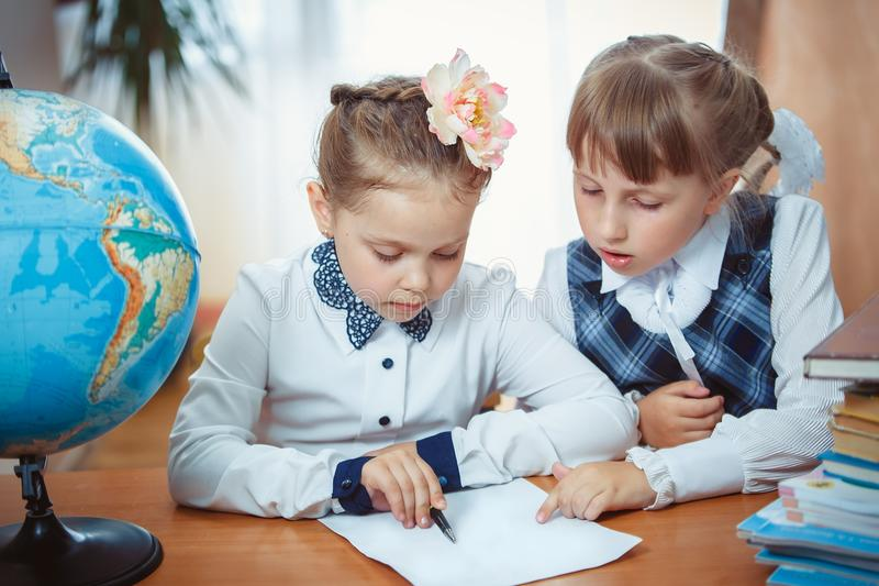 Zwei Schulmädchen sitzen an einem Schreibtisch mit einer Kugel lizenzfreies stockbild
